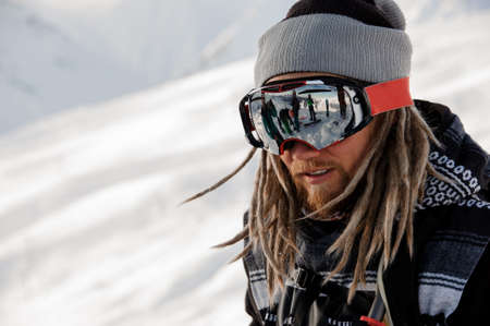 Snowboarder guy with dreadlocks standing on the slope in the protective glasses Stok Fotoğraf