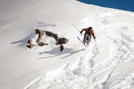 Man skiing down the hill near the rock in the snow