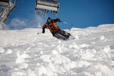 Skier man riding down the hill under the ski lift