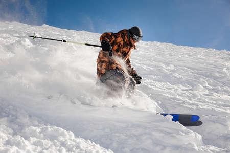 Professional skier man riding down the ski slope