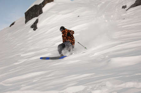 Skier man riding down the snowcovered hill