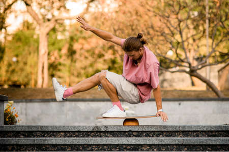 Man balancing squat on the balance board on the concrete steps in the park Stockfoto