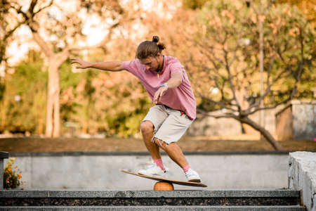 Boy standing on the bending knees on the balance board on the concrete steps in the park