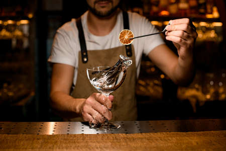 Close-up of bartender decorating splashing alcohol with orange