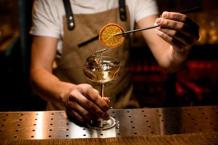 Close-up of bartender adding orange slice in cocktail