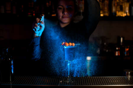 Bartender girl spraying on the cocktail in the glass with fallen berries and flower on the skewer with a bitter