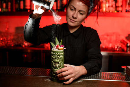 Cute bartender girl serving alcoholic cocktail in the Tiki mug sprinkling on it with sugar powder