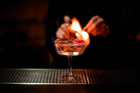 Woman bartender serving on fire alcoholic transparent cocktail with ice in the glass decorated with a pink rose bud