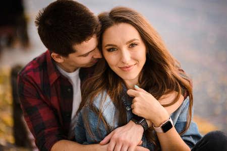 Gelukkig romantisch paar knuffelen zittend op de bank in het herfstpark