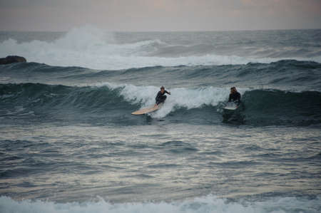 Two man and woman surfers caught a small wave on surf boards Foto de archivo