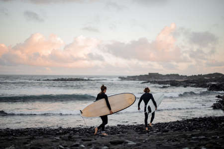 Two man and woman surfers with the surf boards walking on the sea shore