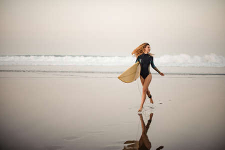 Stunning surfer girl with loose hair running on the sea shore with surfing board Zdjęcie Seryjne