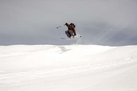 Skier jumps high in the air while gliding down the mountain during overcast weather Zdjęcie Seryjne