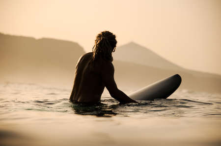 Silhouette of shirtless male surfer with dreadlocks in the waters