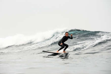 Girl with ponytail surfing the wave on board in the ocean