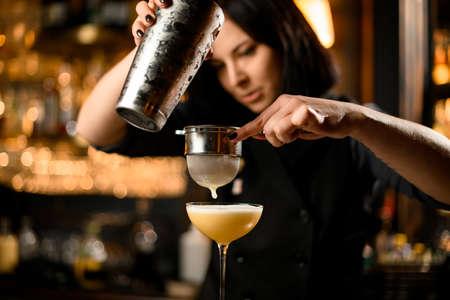 Nette Barkeeperin bereitet Cocktailgetränk mit einem Stahlsieb zu