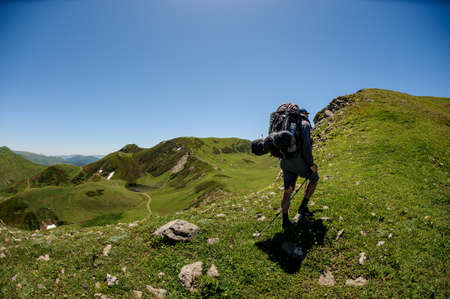 Equipped male tourist hikes on a green hill in good weather Standard-Bild
