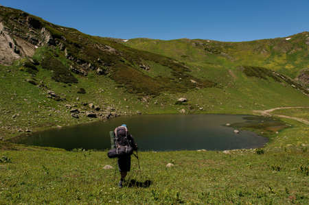Male traveller with backpack walks down to the small pond in hills Standard-Bild