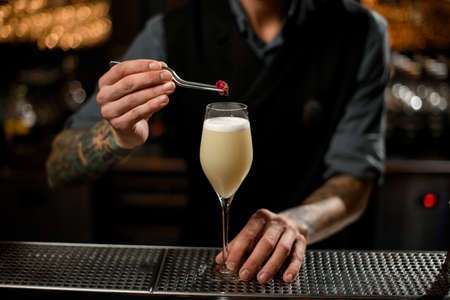 Close-up of bartender adding flower with pincers