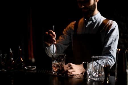 Männlicher Barkeeper, der mit einem speziellen Löffel einen goldenen Cocktail mit Eiswürfeln im Glas rührt