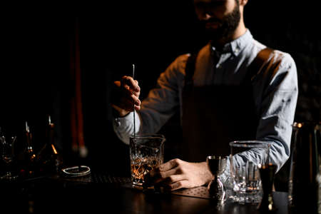 Male bartender stirring a golden cocktail with ice cubes in the glass with special spoon