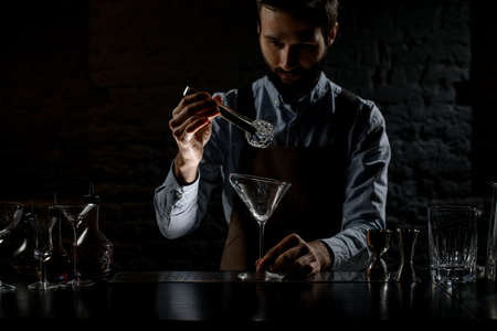 Professional male bartender putting ice cube with twezzers to the tall martini glass