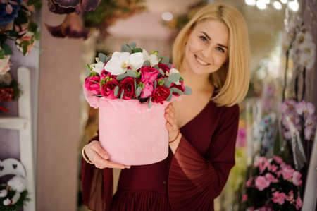 Lovely woman posing with box full of flowers