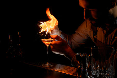 Male bartender spraying on a lighter with orage zest juice to the golden alcoholic drink in a martini glass