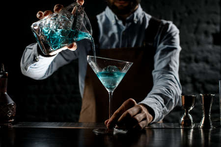 Professional bartender pouring a blue alcoholic cocktail from the measuring cup with strainer to a martini glass Reklamní fotografie