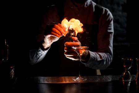 Bartender spraying on a lighter with orage zest juice to golden alcoholic drink in a martini glass Banque d'images - 138367844