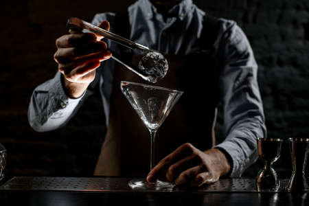 Bartender putting ice cube with twezzers to the tall martini glass Banque d'images - 138367843