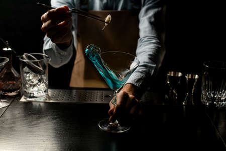 Bartender deacorating a blue alcoholic cocktail in a martini glass with a spikelet with twezzers