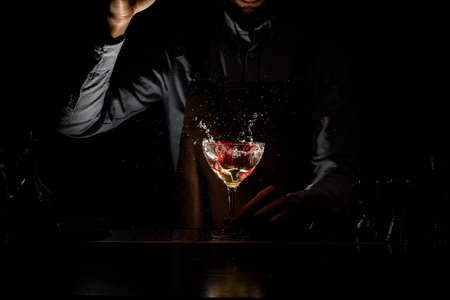 Professional bartender throwing a red rose bud to a martini glass with a cocktail in the dark Foto de archivo