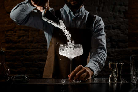 Male bartender putting a crushed ice to the big cocktail glass with special spoon Banque d'images - 138367850