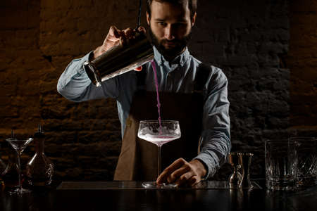 Professional bartender pouring a violet alcoholic drink to the big cocktail glass from the steel shaker Banque d'images - 138367855