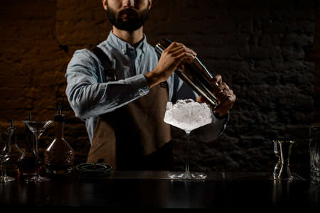 Bartender with a beard holding a steel shaker on the bar counter with the bar equipment Banque d'images - 138367856