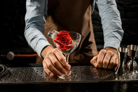 Professional male bartender serving a martini glass with a cocktail decorated with red rose bud Banque d'images - 138367862