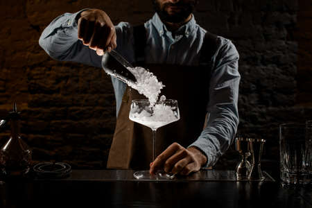 Professional bartender putting a crushed ice to the big cocktail glass with special spoon Banque d'images - 138367863