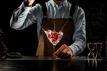Bartender throwing a big red rose bud to a martini glass with a alcoholic cocktail Banque d'images - 138367866