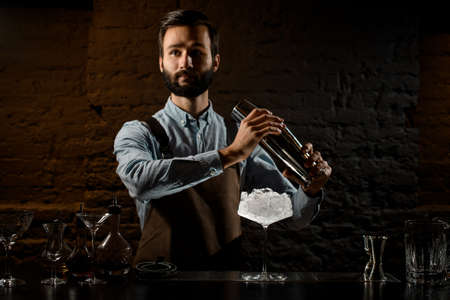 Professional bartender with a beard holding a steel shaker on the bar counter with the bar equipment Banque d'images - 138368201