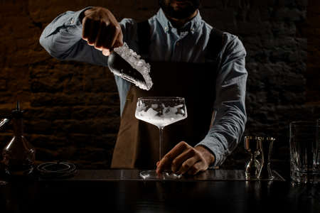 Professional male bartender putting a crushed ice to the big cocktail glass with special spoon Banque d'images - 138368203