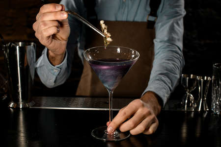 Professional bartender decorated purple alcoholic cocktail in a martini glass with a flower by tweezers Banque d'images - 138368208