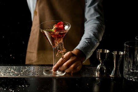 Professional bartender throwing a red rose bud to a martini glass with a cocktail Banque d'images - 138368210
