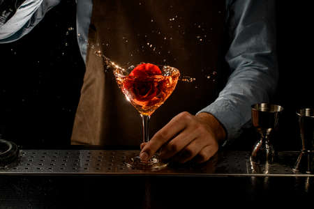 Bartender throwing a red rose bud to a martini glass with a cocktail Banque d'images - 138368212