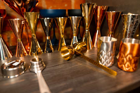 Professional bartender equipment as different metal color jiggers and glasses Banque d'images - 138368214
