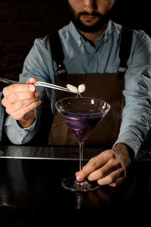 Bartender decorated purple alcoholic cocktail in a martini glass with a flower by tweezers Banque d'images - 138368215