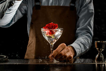 Professional bartender throwing a big red rose bud to a martini glass with a alcoholic cocktail Banque d'images - 138368220