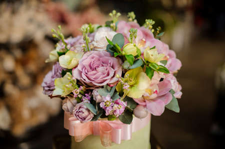 Round shape box full of tender color purple and green flowers in the background of flower shop