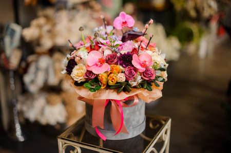 Grey round shape box full of different tender color roses, yellow tulips and pink orchid branch in the background of flower shop