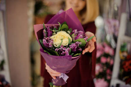 Close-up of gorgeous flower bouquet in purple paper with knot at bottom